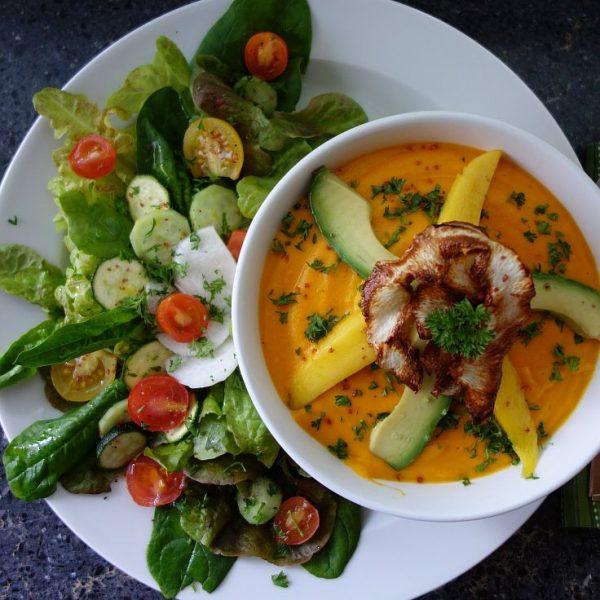 Scharfe Möhrensuppe mit Avocado, Mango und frittiertem Rettich an buntem Salat mit Orangenfilets
